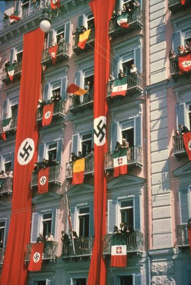 Nazi and Italian flags draped from balconies to welcome Adolf Hitler during state visit to Italy, 1938.