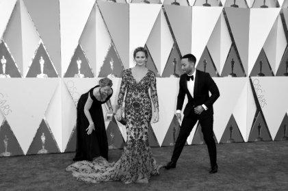 John Legend aiuta la moglie top model Chrissy Teigen a sistemare il vestito assieme a un'assistente