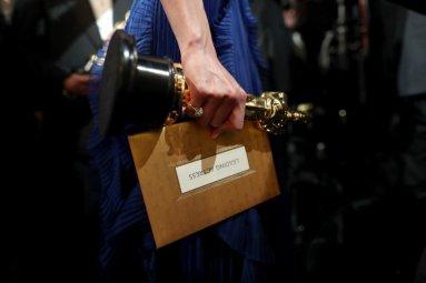 Brie Larson tiene stretta a sé la statuetta e la busta dove c'è scritto il suo nome